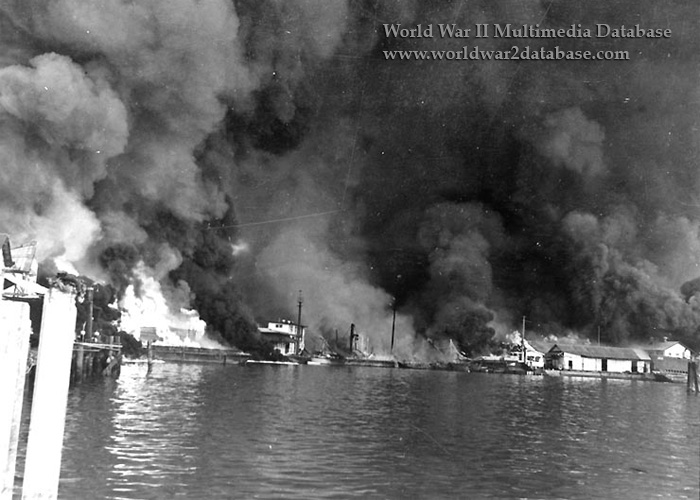 Fires at Cavite Navy Yard resulting from the Japanese air raid on December 10, 1941. Fifty-four bombers of the 11th Air Fleet were detailed from Formosa and attacked at 1300 hours. Twenty-seven attacked ships and small craft in the bay and the remainder went on toward Cavite, dropping their bombs from a height of 20,000 feet, above the range of the nine 3-inch anti-aircraft guns protecting the base. Almost every bomb fell within the Navy Yard. After the first run, the first flight of twenty-seven withdrew and the other twenty-seven bombers, having completed their attack against ships in the bay, flew in to strike the targets. The attack lasted for two hours. The entire yard was set ablaze; the power plant, dispensary, repair ships, warehouses, barracks, and radio station received direct hits. Greatest damage was done by the fire which spread rapidly and was soon out of control. Admiral Rockwell estimated that five hundred men were killed or seriously wounded. The covered self-propelled lighter YF-181 - perhaps visible in the right center - is loaded with almost 200 burning torpedos, which will be consumed in the flames, crippling the offensive capability of the United States Navy Asiatic Fleet's submarines. At the time this photograph was taken, small arms ammunition was exploding in the center of the heavy blaze on the left. The submarine whose bow is visible at the far right is probably USS Sealion (SS-195), hit by bombs and had settled by the stern. Sealion, a 1450-ton Sargo class submarine, was commissioned in late November 1939 and, in the spring of 1940, deployed to the Far East to strengthen the defenses of the Philippines as relations with Japan deteriorated. Sealion was nested at Machina Wharf with USS Seadragon (SS-194) inboard and minesweeper USS Bittern (AM-36) outboard. Most Sealion personnel were below decks. The first stick of bombs landed from 100 to 200 yards (90 to 180 meters) astern of Sealion; all hands were ordered all hands below. On the second