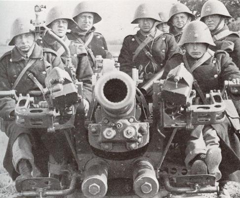 Tropas danesas manejando un cañón antiaéreo. Al igual que en la imagen anterior, pueden apreciarse los característicos cascos.