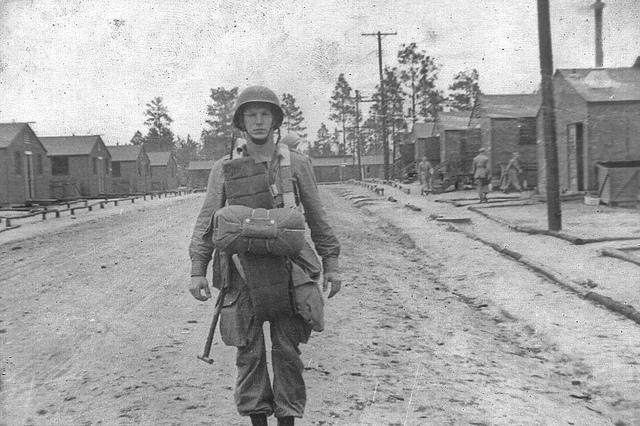 Un paracaidista, cargado con todo su equipo, en la calle central de Camp Toccoa